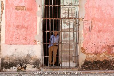 Man standing in gated doorway of an old building in Trinidad Cuba